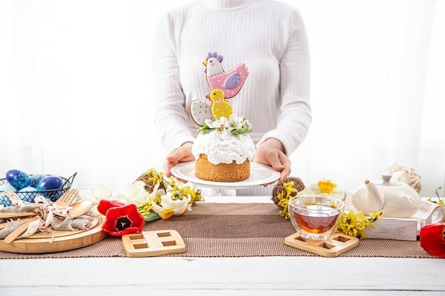 여성의 손은 꽃과 밝은 세부 사항으로 장식 된 축제 부활절 케이크를 들고 있습니다. 부활절 휴가를 준비하는 개념.