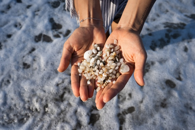 Women's hands are holding a lot of small pebbles