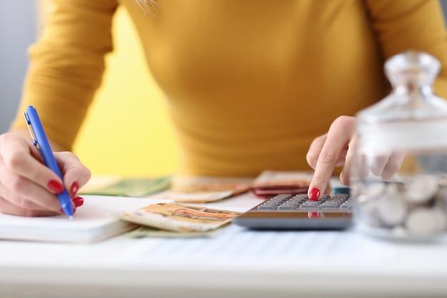 女性の手はペンを持っており、電卓で紙幣を数えています。予算計画の概念