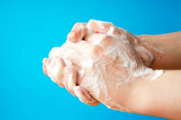 女性の手が石鹸を持っています。手に石鹸の泡。手に黄色い石鹸。女性は青色の背景に手側ビューで石鹸を洗います。ウイルス防止。 covid-19
