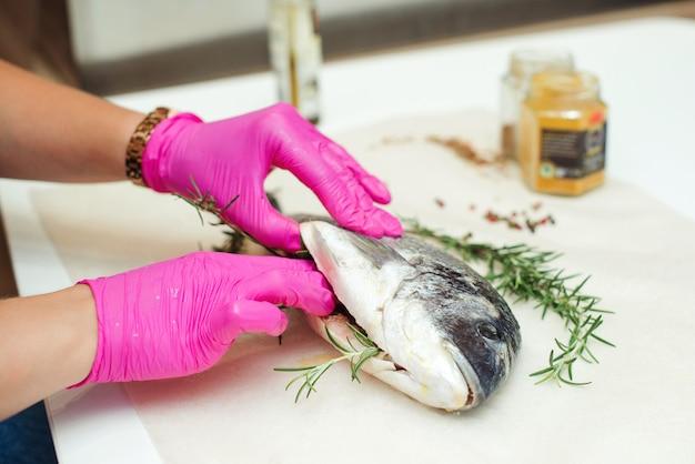 女性の手が夕食にドラダ魚を準備しています。魚料理を調理するための準備。