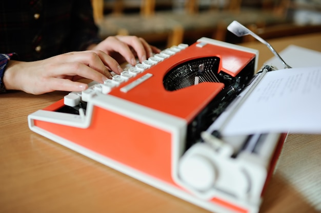 Women's hands are printed on a typewriter in red close-up. writing books