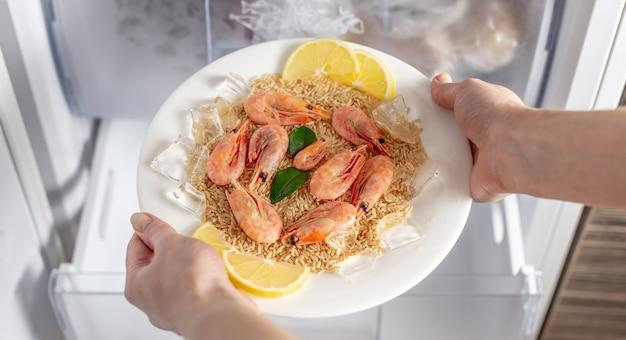 女性の手が冷蔵庫の冷凍庫からご飯、エビ、レモンのプレートを取り出しています
