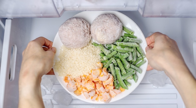 Women's hands are taking a plate of frozen food from the freezer of the fridge