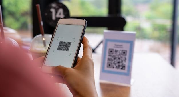 여성의 손은 음식 메뉴를 선택하기 위해 qr 코드를 스캔하기 위해 전화를 사용하고 있습니다. 할인을 받거나 음식 비용을 지불하려면 스캔하세요. 전화를 사용하여 돈을 이체하거나 현금 없이 온라인으로 돈을 지불하는 개념.