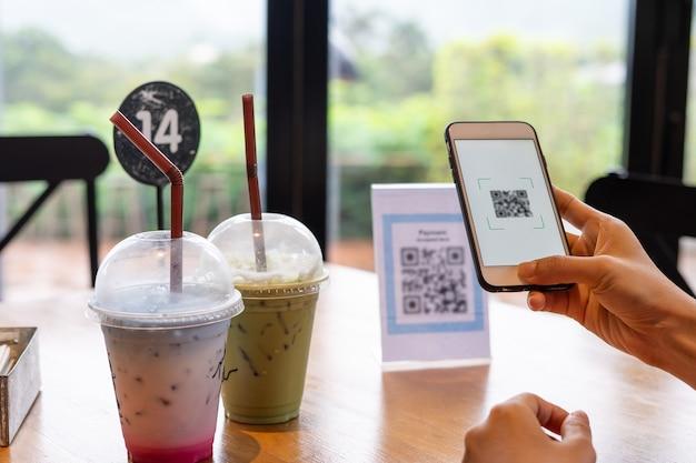 여성의 손이 전화를 사용하여 qr 코드를 스캔하여 음식 메뉴를 선택합니다.