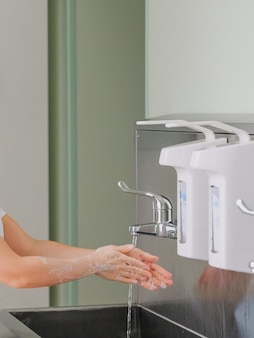 Women's hands are washed with soap under a jet of water over a stainless steel sink.