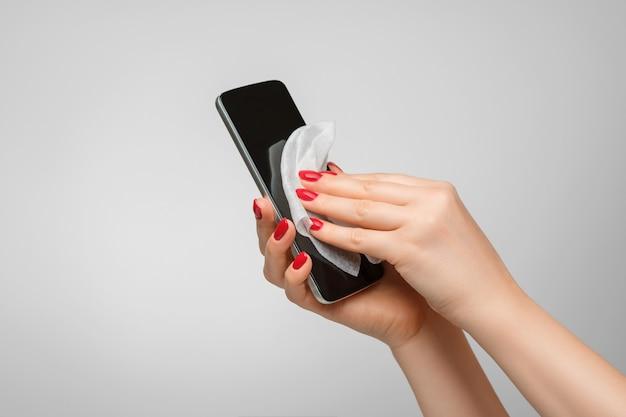 여성의 손이 부드러운 천으로 휴대폰을 닦고 있습니다. 전화의 방부 처리.