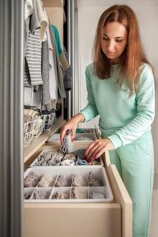 Женские руки заделывают. хранение носков. ящики для нижнего белья.