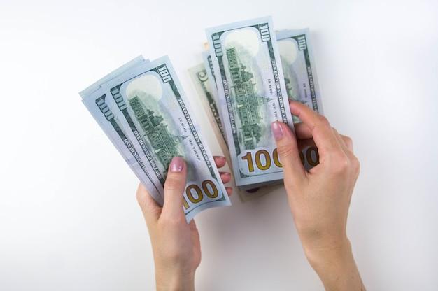 Женские руки считают деньги. женская рука пересчитывает пачку долларов.