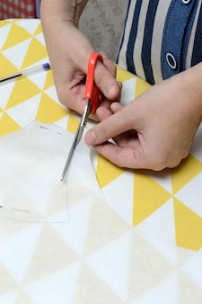 Women's hands cut the fabric with scissors according to the pattern on the table.
