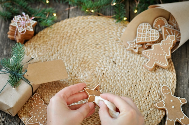 Women's hands decorate christmas gingerbread cookies with sugar frosting on beautiful wooden.