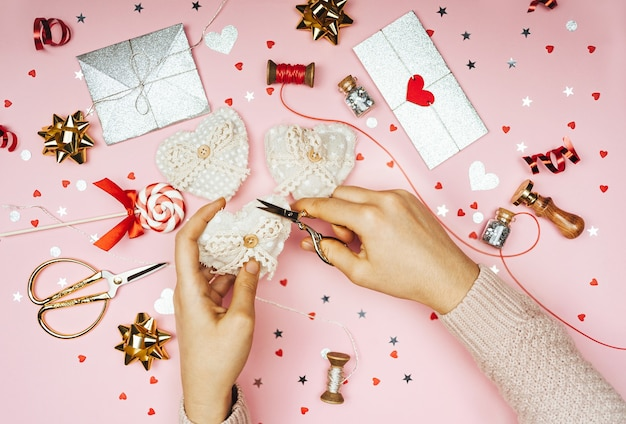 Women's hands decorate crafts in the shape of a heart