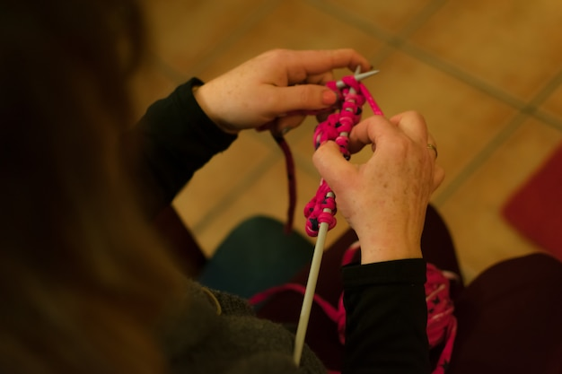 Women's hands doing crochet on a sofa.