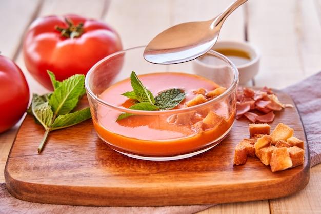 ガスパチョのプレートを食べる女性の手。地中海料理と健康的な食事。