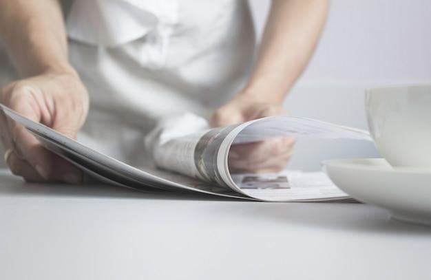 Women's hands flipping through the latest newspaper. news. morning. soft focus
