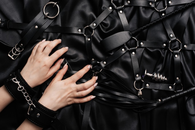 Women's hands in handcuffs on a dark silk sheet next to adult toys