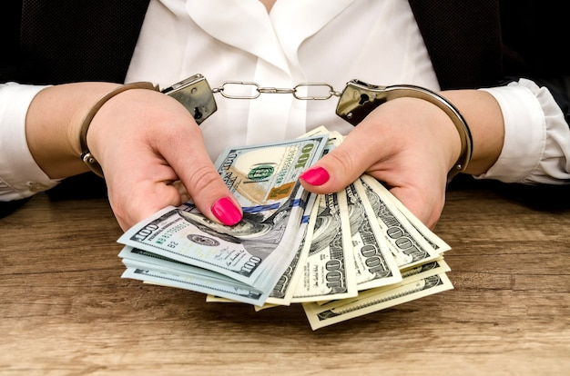 Women's hands in handcuffs with dollars in their hands