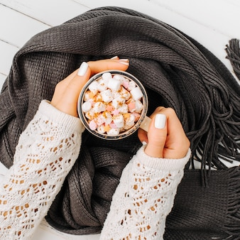 여성의 손은 나무 배경에 스카프로 싸인 커피 한 잔을 들고 있습니다. 가 또는 겨울 개념입니다. 평평한 평지, 평면도