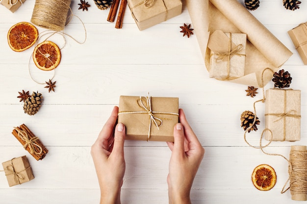 女性の手は、白いテーブルの上の乾燥したオレンジ、シナモン、松ぼっくり、アニスの背景にクラフト紙の贈り物を保持します。