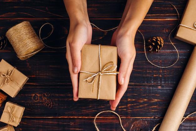 女性の手は、木製のテーブルの乾燥オレンジ、シナモン、松ぼっくり、アニスの背景にクラフト紙の贈り物を保持します。