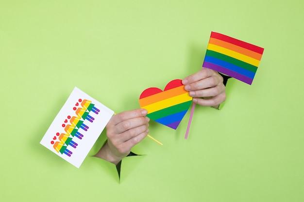 Женские руки держат сердце и флаги цветов радуги на зеленом фоне. концепция лгбт. место для рекламы.