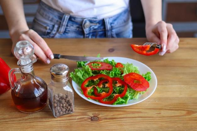 여자의 손은 샐러드 근처에 칼과 포크를 잡고 여자는 야채의 건강 샐러드를 먹는다