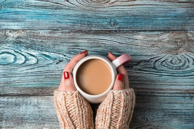 여자의 손은 나무 배경에 뜨거운 커피 음료와 함께 둥근 세라믹 컵을 개최합니다.