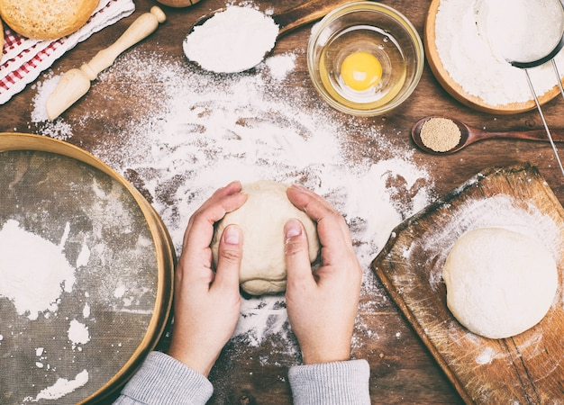 Women's hands hold a ball of yeast dough on a table