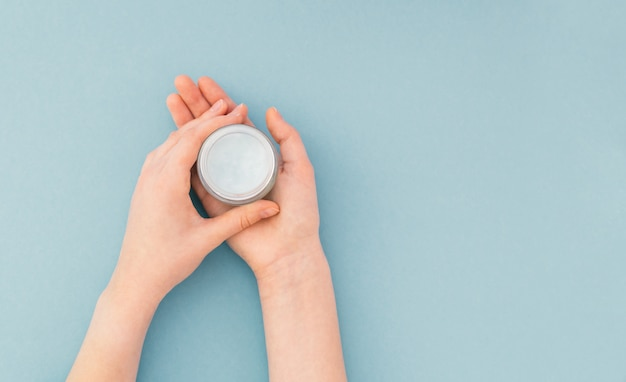 Women's hands hold a bottle with a cream for skin care, on blue