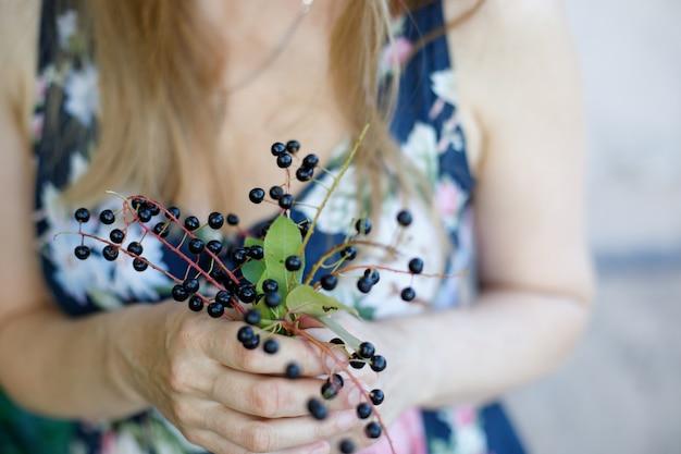 女性の手は桜の実を持っています