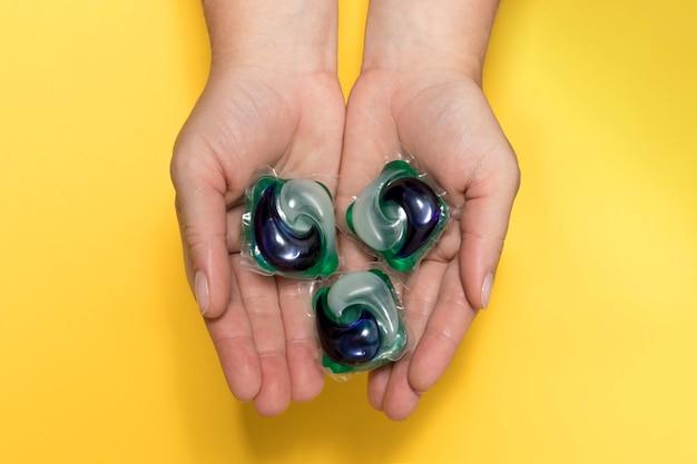 Женские руки держат цветные гелевые капсулы для стирки крупным планом на желтом фоне.