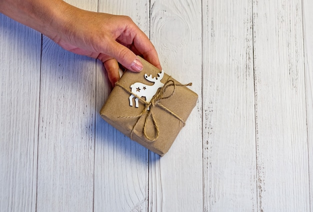 Women's hands hold a craft christmas or new year decorated gift box. light wooden background.