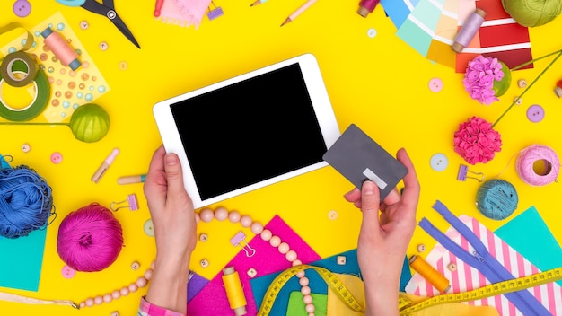 Women's hands hold a credit card and make an online purchase on a tablet. diy workplace with craft equipment on yellow background. mock up.