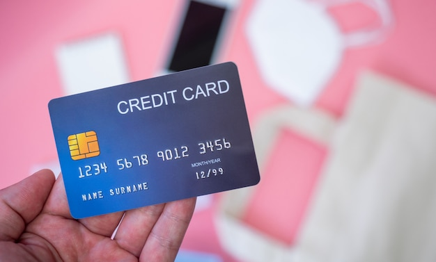 Women's hands hold credit cards with smartphone, surgical mask, credit card, and alcohol gel sanitizer on pale pink background.