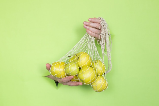 Женские руки держат зеленые яблоки в авоське. место для рекламы.