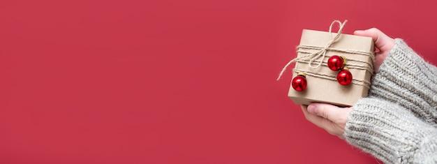 女性の手は、赤い背景、クローズアップ、コピースペースに手作りの贈り物を持っています。ギフトコンセプト、お正月セール、クリスマス割引をご用意しております。クリスマス、新年、テキスト、バナーのためのスペースのある背景。