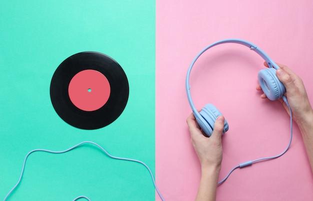 Women's hands hold headphones and vinyl record