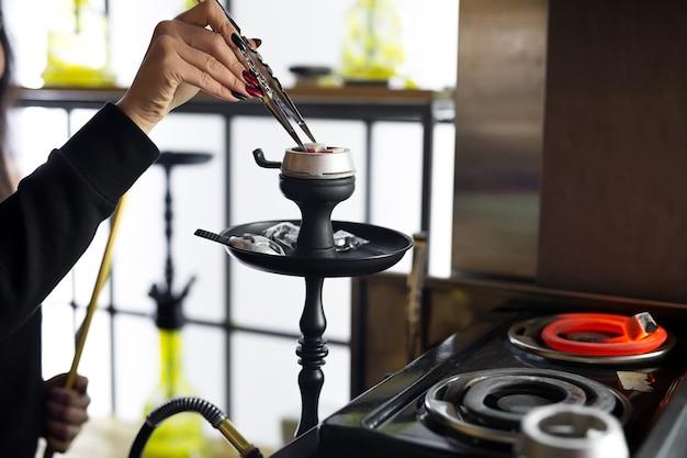 女性の手は水ギセルのトングを持ち、金属製のボウルで熱い石炭を調整します。黒水ギセルはレストランやバーに立っています。