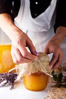 Women's hands hold a jar of honey