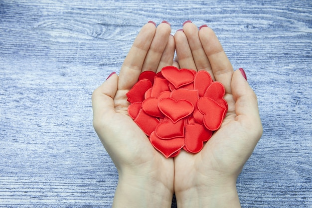 Women's hands hold many red hearts in the palm against the wooden background of jeans color, the concept of saving love
