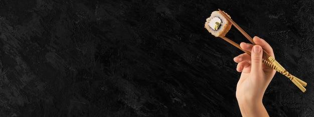 女性の手は棒で巻き寿司を持っています。黒の背景。クリエイティブなコンセプト。