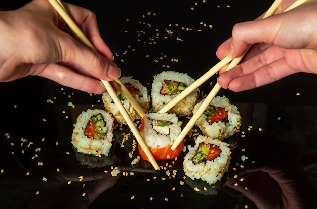 Women's hands hold sushi rolls with sticks. black background. creative concept