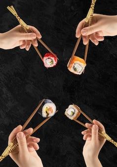 女性の手は棒で巻き寿司を持っています。黒い表面。クリエイティブなコンセプト。
