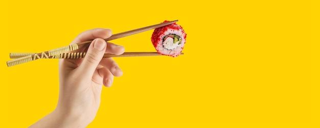 女性の手は棒で巻き寿司を持っています。黄色の背景。クリエイティブコンセプト