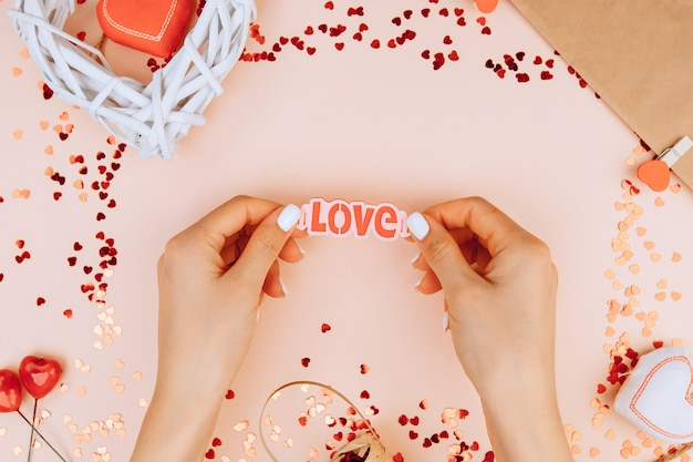 Женские руки держат слово lovevalentine's day background с аксессуарами для вечеринок. концепция дня святого валентина. вид сверху