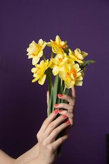 꽃다발을 들고 있는 여성의 손. 봄 꽃 수선화입니다. 여성의 휴일