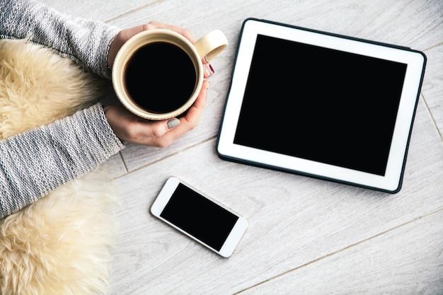大きな一杯のコーヒーを持っている女性の手。近くにはスマートフォン付きの電子タブレットがあります