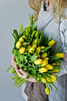 Women's hands holding an armful of yellow tulips.