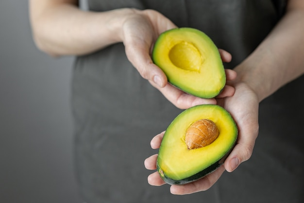 아보카도를 들고 있는 여성의 손, 어두운 티셔츠를 입은 백인 여성, 주방, 요리 셰프, 익고 맛있는 아보카도, 건강하고 건강한 음식, 날 과일과 채소 채식주의자